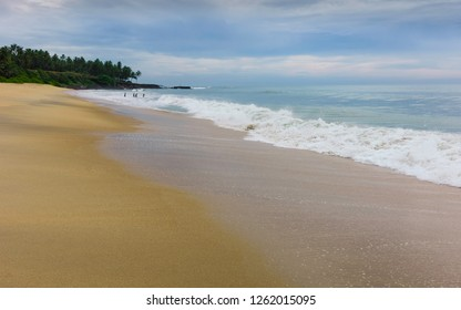 Kannur, Kerala, India. Coastline along sandy beach flanked by calm waters of Arabian Sea and a few palm tress and swimmers on horizon at dusk on Thottada beach, Kannur, Kerala, India.