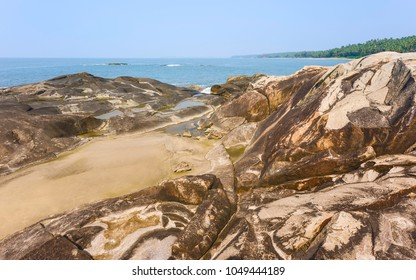 Kannur, Kerala, India. A large rocky outcrop, Chera Rock, along palm tree lined beach and Arabian Sea on bright day near Kannur, Kerala, India.