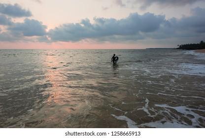 Kannur, Kerala, India. A mollusc fisherman emerges from Arabian Sea on a beautiful evening at sunset along Thottada beach near Kannur, Kerala, India.