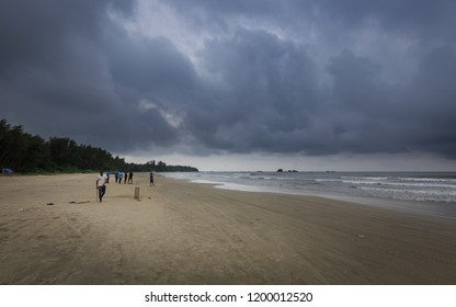 KANNUR, KERALA, INDIA - October 01, 2017: Cricket players at Muzhappilangad drive-in beach in a cloudy day, Kannur, Kerala, India, This is the longest Drive-In Beach in Asia.