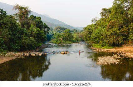 Kannur, Kerala, India. River Periyar at dawn flanked by forest against backdrop of Cardamom hills in late winter near Kannur, Kerala, India.