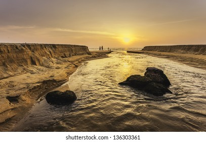 Kannur, Kerala, India. Sunset as Thottada river carves a channel through the sandy beach at Thottada village and spills into Arabian Sea, 10 km south of Kannur, north Kerala, India.