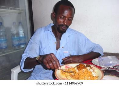 "KANO,  NIGERIA - CIRCA OCTOBER 2010 : Unidentified local muslim man eating ""jollof rice"" at the local restaurant."