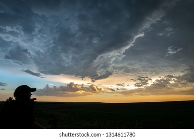 Kanorado, Kansas / United States - May 27th 2018: Silhouette of a storm chaser watching a severe thunderstorm over the Great Plains at sunset.