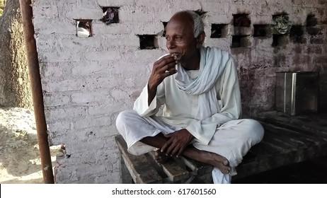 KANPUR, UTTAR PRADESH, INDIA - 26 MARCH, 2017: An Indian poor rural old man sitting at tea stall and drinking tea wearing white traditional Indian village dress (DHOTI-KURTA).