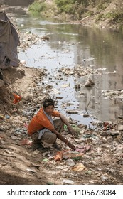 Kanpur, Uttar Pradesh / India - Mar 23 2012: Concept of Water pollution, garbage, water crisis and poverty. An  Indian by sitting near water passage.
