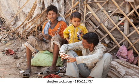 Kanpur, Uttar Pradesh / India - Mar 23 2012: Concept of poverty, homeless. A poor family, father and two sons, in the rural area of India.