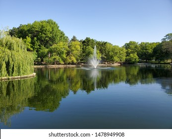 Kansas City, Missouri / USA - June 13 2019: Fountain and Reflection in Lake at Loose Park on Sunny Spring Day