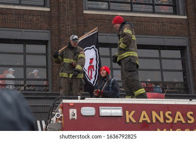 Kansas City, MO / United States of America - February 5th, 2020 : Firefighters atop a firetruck with a KC Chiefs flag in preparation for the Chiefs Kingdom Championship Parade, fans in windows behind