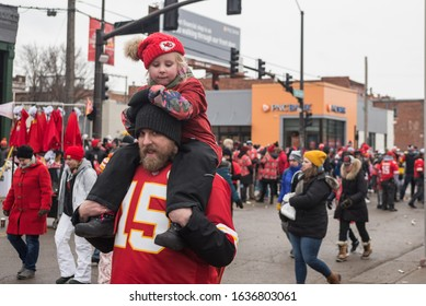 Kansas City, MO / United States of America - February 5th, 2020 : A father carries his daughter on his shoulders after the Chiefs Kingdom Championship Parade.  Both wearing Chiefs clothing.