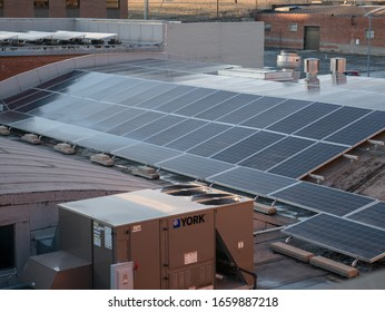 Kansas City, MO / United States of America - February 18th, 2020 : Solar panels on rooftop of a commercial building, in late afternoon, not in direct sunlight.