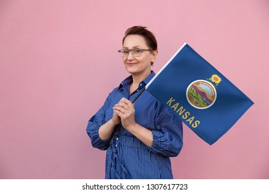 Kansas flag. Woman holding Kansas state flag. Nice portrait of middle aged lady 40 50 years old holding a large state flag over pink wall background on the street outdoor.