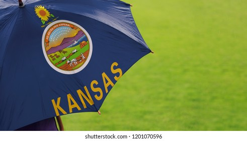 Kansas state flag umbrella. Closeup of a printed umbrella over green field/lawn background. Rainy weather / climate change and global warming concept.