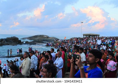 KANYAKUMARI, INDIA - APR 19: Unidentified pilgrims watch sunrise at Triveni Sangam as the sun rises near Vivekananda Rock Memorial and Thiruvalluvar Statue on April 19, 2015, Kanyakumari, India.