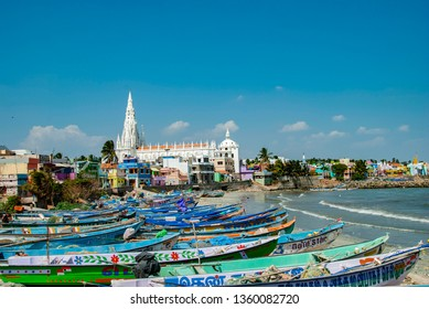 Kanyakumari, India - January 26,2019:Our Lady of Ransom Shrine Church behind colorful houses on a sand beach occupied by fishing boats in Kanyakumari in India