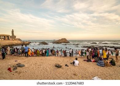 Kanyakumari, Tamil Nadu, India. 03/28/2014. People on the beach watching the sunset at Kanyakumari, India with Thiruvalluvar Statue at the back
