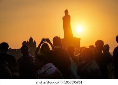 Kanyakumari, Tamil Nadu, India - February 12, 2017 : Unidentified tourists take a picture of sunrise view of Swami Vivekananda Memorial rock and thiruvalluvar island in Kanyakumari, India