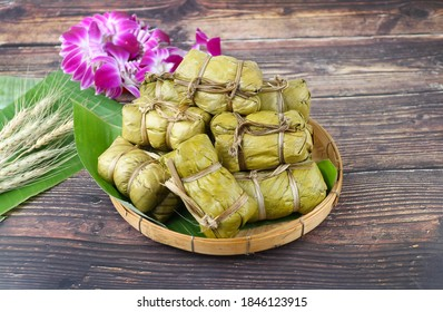 Kao tom mud- Stemed sticky rice filled with banana and wrapped with banana leaf in bamboo basket on the wooden background - Thai dessert/snack