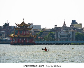Kaohsiung, Taiwan - 04 Oct 2018: People canoeing on Kaohsiung Lotus lake in front of traditional chinese Pagoda and temple. Kaohsiung Watersport . City in Background
