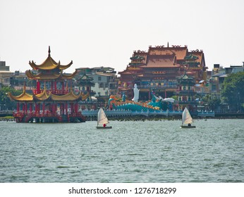Kaohsiung, Taiwan - 04 Oct 2018: Wind surfers on Kaohsiung Lotus lake in front of traditional chinese Pagoda and temple. People surfing. Kaohsiung Watersport . City in Background