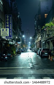 Kaohsiung, Taiwan - 16 April 2019: A dark, urban alley at a rainy night with the Tuntex Sky Tower 85 at the end of the street. Lights reflecting on wet tarmac
