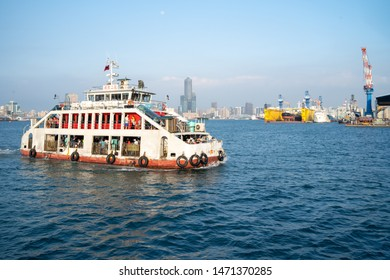 Kaohsiung, Taiwan - 17 April 2019: Cijin Island ferry on sunny sommer day on the water way to the CiJin island with the skyline of Kaohsiung in the background
