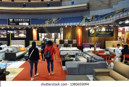 KAOHSIUNG, TAIWAN -- APRIL 5, 2019: People look at living room sets and beds at a furniture promotion event.