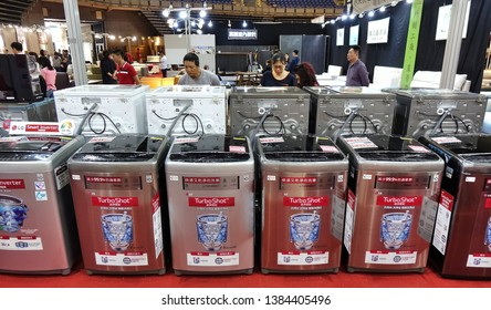 KAOHSIUNG, TAIWAN -- APRIL 5, 2019: Visitors at a sales and promotional fair for electric household appliances look at washing machines.
