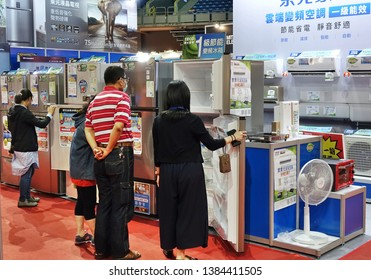 KAOHSIUNG, TAIWAN -- APRIL 5, 2019: Visitors at a sales and promotional fair for electric household appliances look at refrigerators.