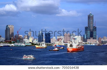 KAOHSIUNG, TAIWAN -- AUGUST 13 , 2017: A busy scene with freight ships and tugboats in Kaohsiung port. In the back one can see the skyline of the city.