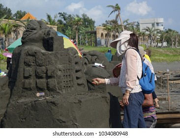 KAOHSIUNG, TAIWAN -- AUGUST 5, 2017: Artists work on sand sculptures at the 2017 Black Sand Beach festival on Chijin Island.