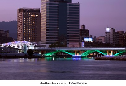 KAOHSIUNG, TAIWAN -- DECEMBER 1, 2018: Evening view of the Love River with the illuminated light rail bridge and the True Love Pier station.