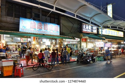 KAOHSIUNG, TAIWAN -- DECEMBER 22, 2018: Tourists visit the outdoor shopping and restaurant area on Qijin Island, famous for its seafood.