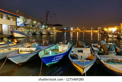 KAOHSIUNG, TAIWAN -- DECEMBER 22, 2018: A small fishing harbor by night on the island of Qijin. In the back are colorful fuel storage tanks.