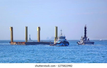 KAOHSIUNG, TAIWAN -- DECEMBER 22, 2018: A tugboat pulls a large floating steel construction element into the port of Kaohsiung.