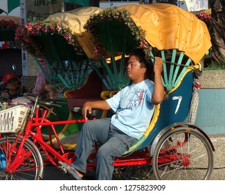 KAOHSIUNG, TAIWAN -- DECEMBER 22, 2018: A driver for a traditional cycle rickshaw rests in the afternoon sun while waiting for passengers.