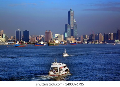 KAOHSIUNG, TAIWAN -- DECEMBER 22, 2018: Tourist boats take visitors on a cruise across Kaohsiung Port. In the back is the skyline of the city.