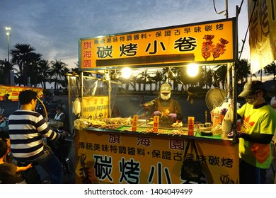 KAOHSIUNG, TAIWAN -- DECEMBER 22, 2018: A street vendor cooks grilled squid near the beach on Cijin Island.