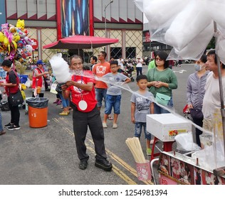 KAOHSIUNG, TAIWAN -- DECEMBER 8, 2018: A street vendor demonstrate his skills at making cotton candy at a local outdoor event.