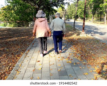 Kaohsiung, Taiwan, February 10, 2021: An old couple holding hands walking on a stone road with golden leaves