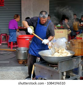 KAOHSIUNG, TAIWAN -- FEBRUARY 17, 2018: A man at an outdoor food stall cooks fried rice in a large wok.