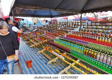 KAOHSIUNG, TAIWAN -- FEBRUARY 6, 2019: People try to throw bamboo rings over bottles in a skill game at a Chinese New Year Market.