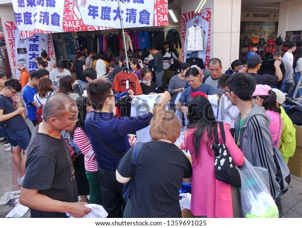 KAOHSIUNG, TAIWAN -- FEBRUARY 6, 2019: People snap up cheap shirts and clothing that is for sale at an outdoor market.