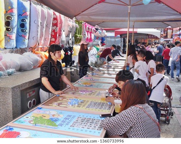 KAOHSIUNG, TAIWAN -- FEBRUARY 6, 2019: People play Bingo at an outdoor market hoping to win prizes such as stuffed animals and cartoon merchandise.