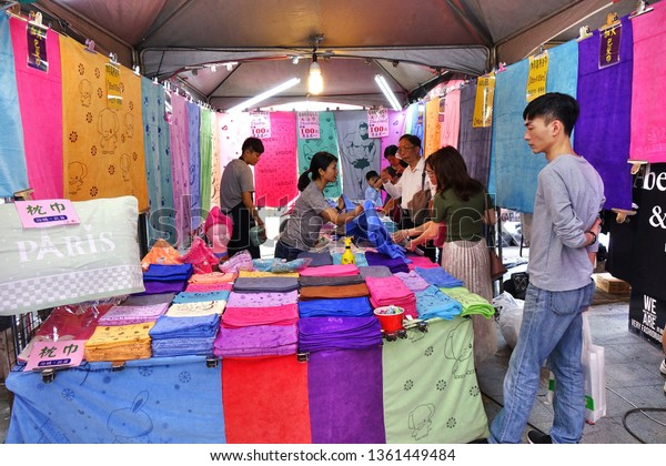 KAOHSIUNG, TAIWAN -- FEBRUARY 6, 2019: An outdoor market stall sells bath towels in various colors and sizes.