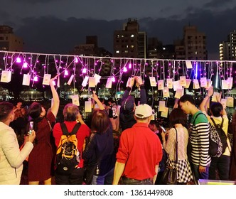 KAOHSIUNG, TAIWAN -- FEBRUARY 9, 2019: People hang up wish cards during the 2019 Lantern Festival on the banks of the Love River.
