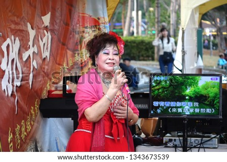 KAOHSIUNG, TAIWAN -- FEBRUARY 9, 2019: A female performer sings Karaoke songs on the banks of the Love River during the Lantern Festival.