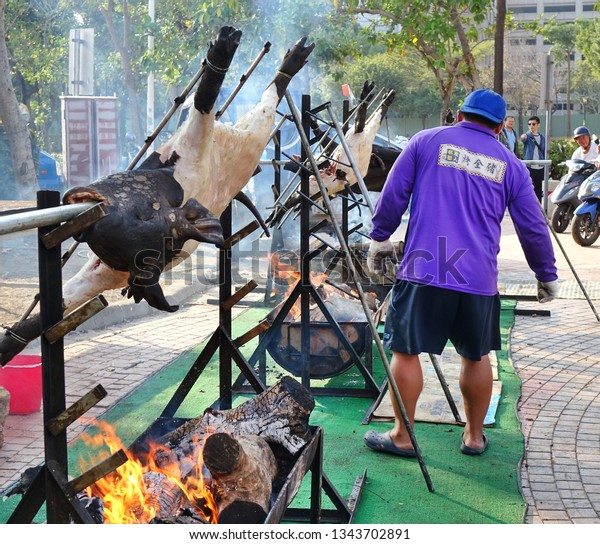 KAOHSIUNG, TAIWAN -- FEBRUARY 9, 2019: A member of Taiwan's indigenous people roasts whole pigs on the banks of the Love River during the Lantern Festival.