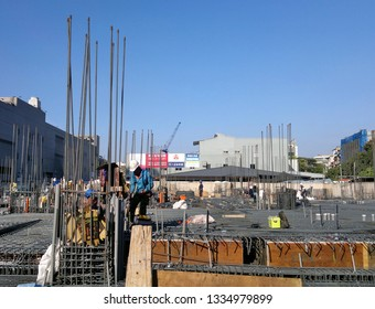 KAOHSIUNG, TAIWAN -- JANUARY 22, 2019: Workers at an apartment construction site prepare steel bars for reinforced concret application.