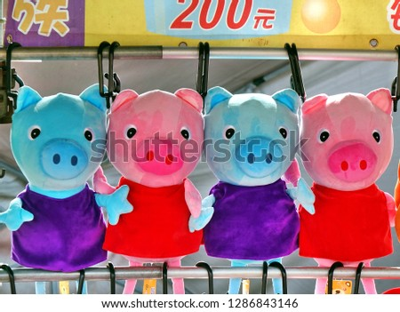 KAOHSIUNG, TAIWAN -- JANUARY 5, 2019: An outdoor skill game stall offers television animation character Peppa Pig merchandise for prizes to those who win.
